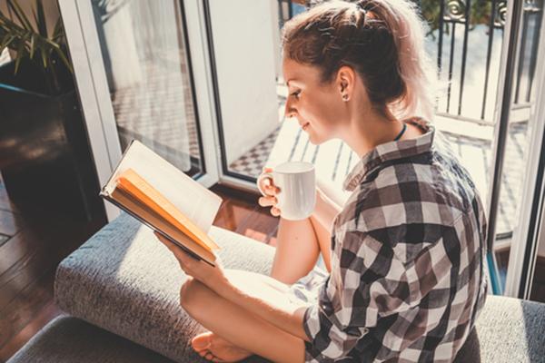 Mujer lee libro con luz natural