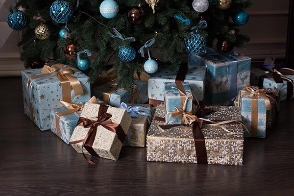 Regalos envueltos en oro y azul bajo el árbol