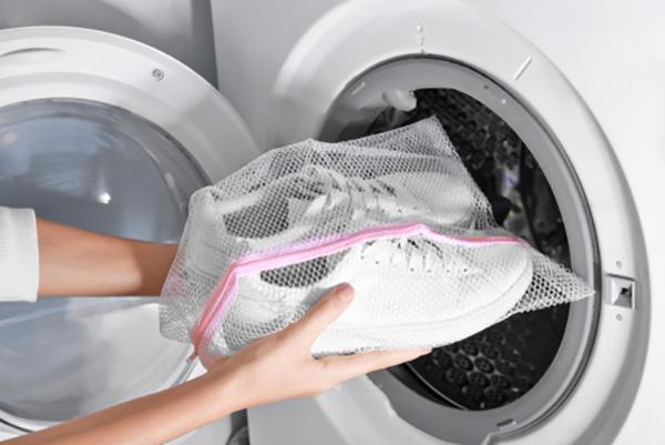 Zapatos en bolsa de malla en lavadora