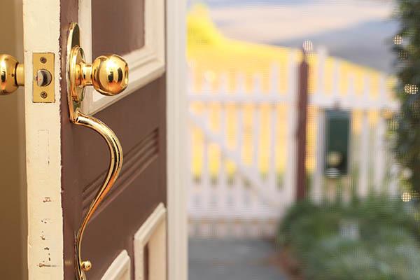 Puerta delantera marrón abierta con herrajes dorados