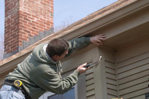 Hombre arreglando el revestimiento de la casa