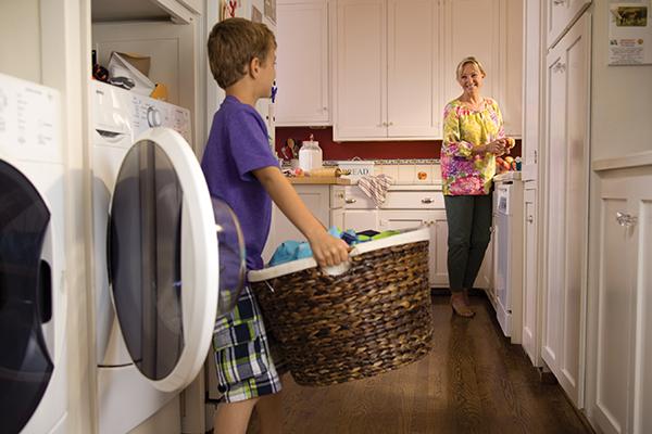 Joven con canasta de lavandería de pie delante de la lavadora