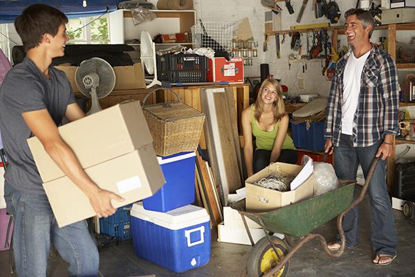 Papá y dos hijos adolescentes organizando garaje