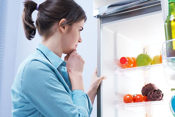 Mujer mirando al congelador
