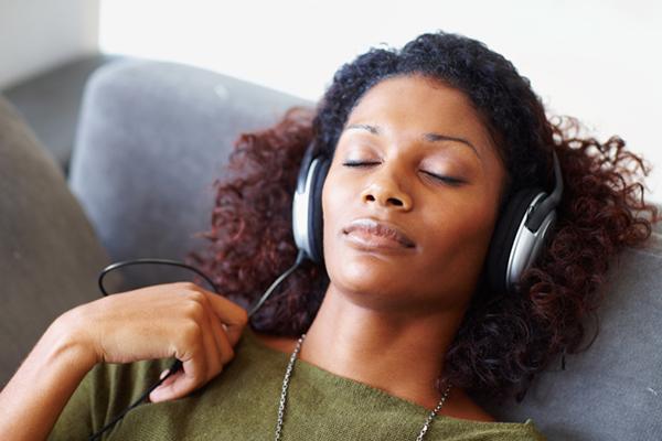 Mujer que usa audífonos sobre la oreja escucha música para aliviar el estrés