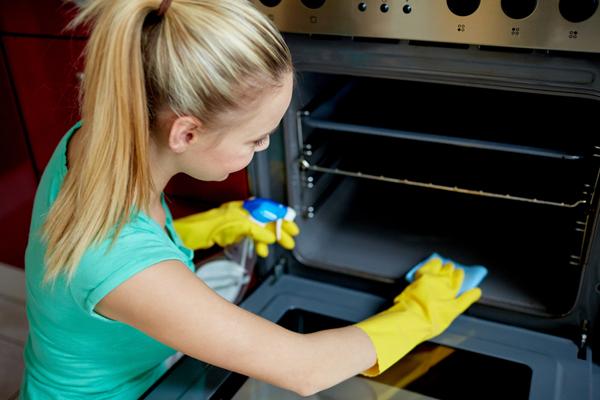 Mujer limpia el interior del horno
