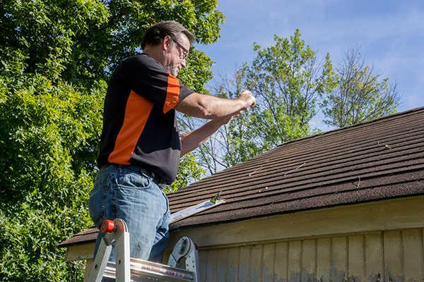 Hombre en escalera reparando un techo con goteras