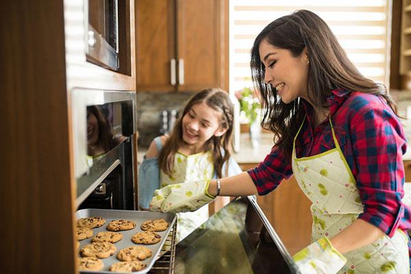 Mamá y niño horneando galletas en el horno