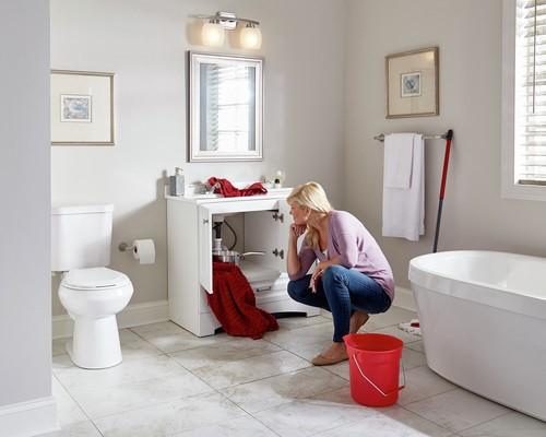 Mujer comprobando si hay moho debajo del fregadero con fugas