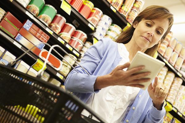 Mujer en la tienda de abarrotes mira a través de la lista de abarrotes en un dispositivo inteligente